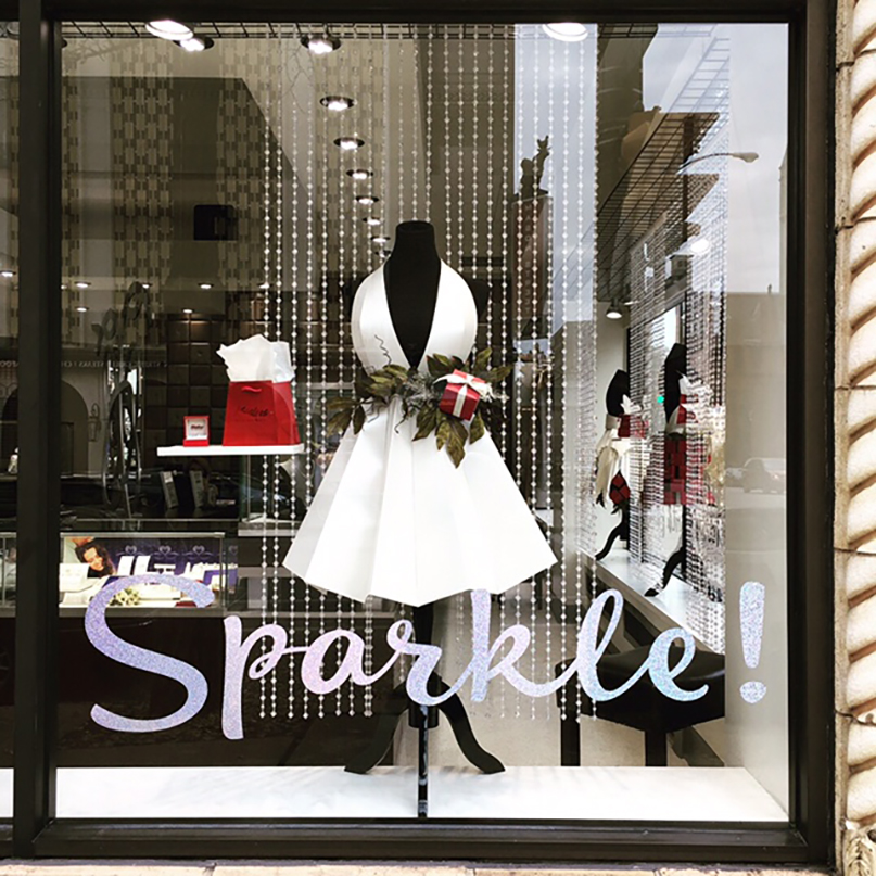 Holiday window display at jewelry store featuring paper dress on mannequin, designed by Retailworks Inc.